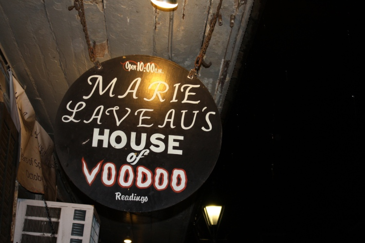 A sign advertising Marie Laveau's House of Voodoo on Bourbon Street in New Orleans.